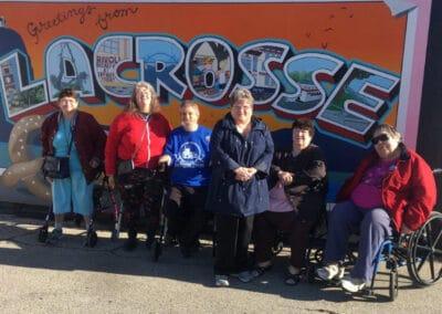 La Crosse Housing Authority Resident Activity | Photo in front of La Crosse billboard